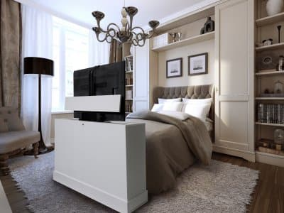 White TV lift cabinet at the foot of the bed in a contemporary bedroom, HDTV fully raised into viewing position